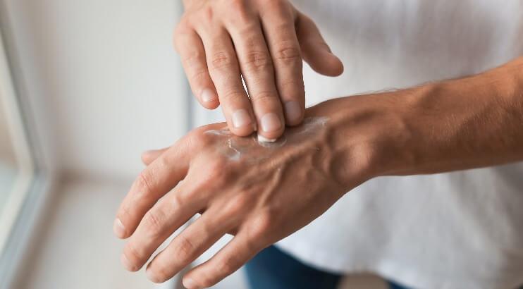 男性が手を保湿ケアする